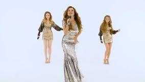 Três meninas bonitas estão cantando no estúdio Estão em um fundo isolado branco video estoque