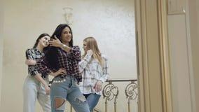 Três meninas bonitas estão na pose em escadas na casa lentamente filme