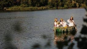 Três meninas bonitas na roupa eslavo em um barco no rio passagem das mulheres um ramalhete dos wildflowers Menina vídeos de arquivo