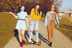 Três meninas bonitas no hoverboard Relacionamentos das amigas, caminhada, tecnologias modernas ativas, novas As meninas ensinam a fotos de stock royalty free