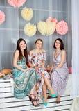 Três meninas bonitas novas em vestidos coloridos brilhantes Mola mo Foto de Stock