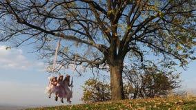 Três meninas bonitas que balançam em um balanço sob uma árvore grande filme