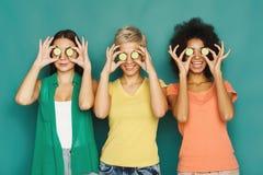 Três meninas bonitas que cobrem os olhos com as partes do pepino Foto de Stock