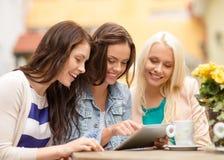 Três meninas bonitas que olham o PC da tabuleta no café imagem de stock royalty free