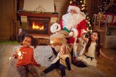 Três meninas brincalhão com Santa Claus na atmosfera do Natal imagens de stock royalty free