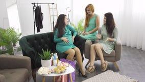 Três meninas caucasianas em vestidos leves conversando na sala de estar Mulheres passam tempo com a amiga grávida vídeos de arquivo