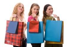 Três meninas com sacos de compra. Isolado no branco Fotos de Stock Royalty Free