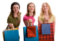 Três meninas com sacos de compra. Isolado no branco Fotografia de Stock