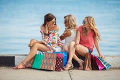 Três meninas com sacos de compras e vão comprar Fotos de Stock