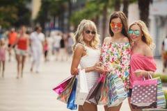 Três meninas com sacos de compras e vão comprar Fotografia de Stock Royalty Free