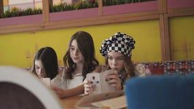 Três meninas consideravelmente alegres que tomam selfies no café 4K filme
