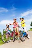 Três meninas da criança que guardam bicicletas fora Foto de Stock Royalty Free