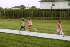 Três meninas da irmã que jogam o funcionamento no parque imagens de stock