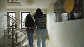 Três meninas despreocupadas que correm acima em escadas na casa luxuoso lentamente vídeos de arquivo