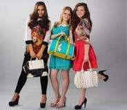 Três meninas do estilo diferente que levantam para anunciar fotografia de stock