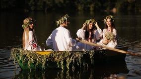 Três meninas e um indivíduo no vestido nacional eslavo que flutua em um barco Meninas nas grinaldas em um barco Tradição nacional vídeos de arquivo