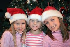 Três meninas em chapéus de Santa. Fotos de Stock