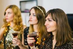 Três meninas em um partido com bebidas em suas mãos, foco no Foto de Stock