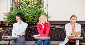 Três meninas fazem coisas diferentes maneiras diferentes de relaxar Meninas no caf? Diversidade social M?sica de escuta Livro de  imagem de stock royalty free