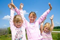 Três meninas felizes com mãos levantadas. Imagem de Stock
