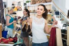 Três meninas guardando os sacos de compras de papel no boutique imagens de stock