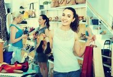 Três meninas guardando os sacos de compras de papel no boutique fotografia de stock
