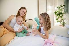 Três meninas jogam irmãs na manhã no quarto fotos de stock