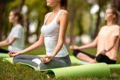 Três meninas magros novas sentam-se nas posições dos lótus com os olhos de fechamento que fazem a ioga sobre esteiras da ioga sob imagens de stock royalty free