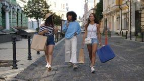 Três meninas multi-étnicos que andam com sacos de compras vídeos de arquivo