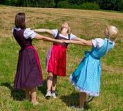 Três meninas na dança do Dirndl Fotografia de Stock Royalty Free