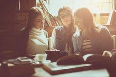 Três meninas novas felizes dos estudantes que trabalham trabalhos de casa junto no li imagem de stock