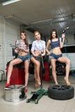Três meninas para o pneu Reparo do carro imagem de stock royalty free