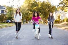 Três meninas pre-adolescentes nos 'trotinette's e na bicicleta que olham à câmera foto de stock
