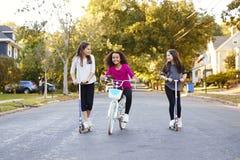 Três meninas pre-adolescentes que montam na rua em 'trotinette's e em uma bicicleta fotos de stock