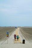 Três meninas que andam afastado em um passeio à beira mar Imagem de Stock Royalty Free