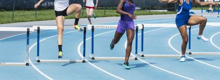 Três meninas que competem os obstáculos de 400 medidores Fotografia de Stock Royalty Free
