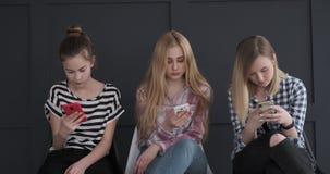 Três meninas que conversam usando seus telefones celulares