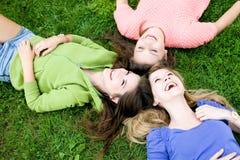 Três meninas que encontram-se na grama Fotos de Stock