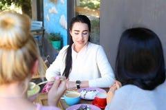 Três meninas que falam e sentam-se no café Moça bonita com blac Foto de Stock