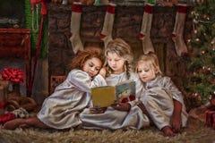 Três meninas que leem o livro da história do Natal Foto de Stock Royalty Free