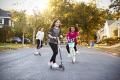 Três meninas que montam abaixo da rua em 'trotinette's e em uma bicicleta fotografia de stock