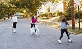 Três meninas que montam em 'trotinette's e em uma bicicleta na rua fotos de stock