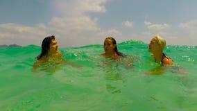 Três meninas que nadam na câmera pov da ação do mar da jovem mulher que fala na água azul na praia bonita video estoque