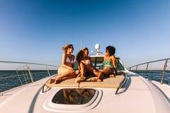 Três meninas que penduram para fora em uma plataforma privada do iate fotos de stock