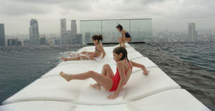Três meninas que têm o divertimento na piscina fotos de stock royalty free