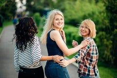 Três meninas que têm o divertimento no parque do por do sol Vista traseira Foto de Stock