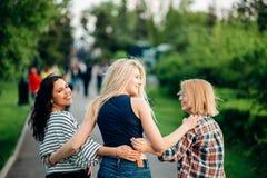Três meninas que têm o divertimento no parque do por do sol Vista traseira Imagens de Stock Royalty Free
