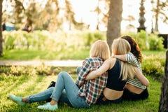 Três meninas que têm o divertimento no parque do por do sol Vista traseira Imagem de Stock