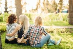 Três meninas que têm o divertimento no parque do por do sol Vista traseira Imagens de Stock