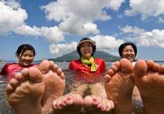 Três meninas relaxam na água na praia Fotografia de Stock